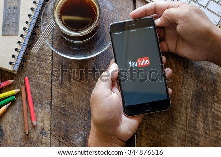 CHIANG MAI,THAILAND, NOV - 29 -2015 : Brand new Apple iPhone 6 plus with YouTube app on the screen lying on old wood desk with headphones. YouTube is the popular online video sharing website  - stock photo