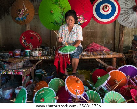 CHIANG MAI, THAILAND - NOVEMBER 22, 2015: An unidentified woman paints an umbrella in parasol factory in Chiang Mai, Thailand. This is a traditional craft that attracts local and foreign visitors. - stock photo