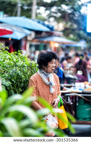 CHIANG MAI, THAILAND  - NOVEMBER 15, 2014: Asian old lady selling in Chiang Mai, Thailand.