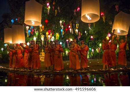 CHIANG MAI, THAILAND - NOVEMBER 07, 2014: Groups of Buddhist monks launch sky lanterns at the Yee Peng festival of lights at a nighttime ceremony.