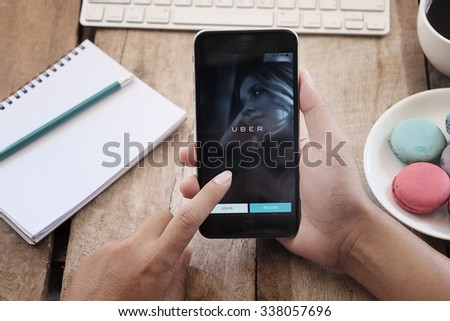 CHIANG MAI,THAILAND - OCT 02,2015 : A man hand holding Uber application showing on Apple iPhone 6 plus,Uber is smartphone app-based transportation network. - stock photo