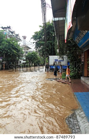 CHIANG MAI THAILAND - SEPTEMBER 29 : Flooding in Chiangmai city.Flooding of buildings near the Ping River on September 29,2011 in Chiangmai, Thailand. Unidentified kids - stock photo