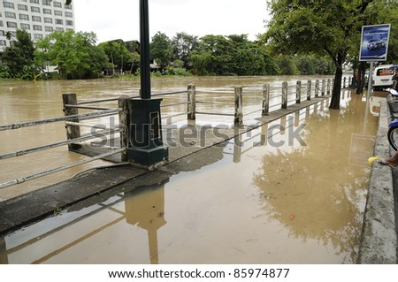 CHIANG MAI THAILAND - SEPTEMBER 28 : Flooding the Chiangmai city.Ping flowing rivers are overflowing the sidewalk quickly on September 28,2011 in Chiangmai Thailand - stock photo