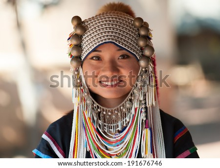 CHIANG RAI, THAILAND - DEC 4, 2013: Unidentified Akha girl in traditional clothes and silver jewelery in akha hill tribe minority village near Chiang Mai. Young asian woman with smile on face - stock photo