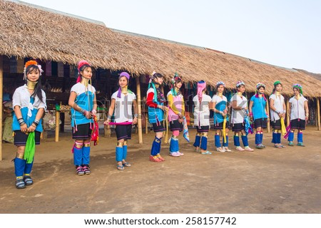 CHIANG RAI, THAILAND - JAN 2015: Karen tribal girls dressed in traditional costumes  performing national dance  Padaung village, Thailand.  Long neck tribe village originate from neighbouring Myanmar. - stock photo