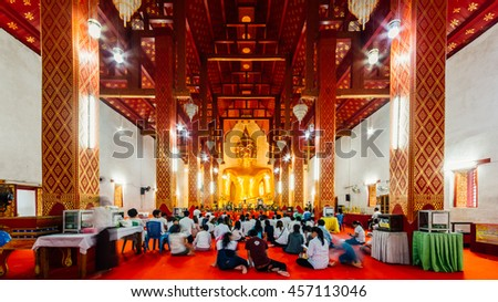 CHIANG RAI, THAILAND - JULY 19, 2016: Thai monks and buddhist pray Buddha statue at Wat Sri Kom Kam in Phayao, Thailand. Day is the important Buddhist.
