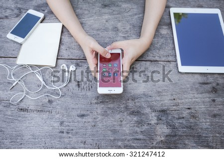 CHIANG RAI, THAILAND - SEPTEMBER 13, 2015: Woman holding Apple iphone show all of popular social media icons on smartphone device screen background. - stock photo