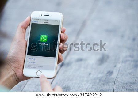 CHIANG RAI, THAILAND - SEPTEMBER 13, 2015: Woman try to use social Internet service WhatsApp screen on blue background. iPhone 6 was created and developed by the Apple inc. - stock photo