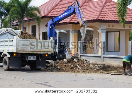 CHIANGMAI, SEPTEMBER 28: The worker controls the backhoe shovel to load the earth on the ground to unload on the truck on September 28, 2014 in Chiangmai, Thailand. - stock photo