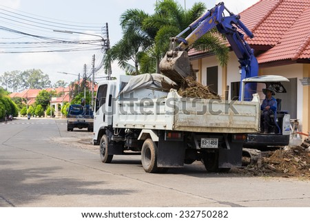 CHIANGMAI, SEPTEMBER 28: The worker controls the backhoe shovel to unload the earth on the truck on September 28, 2014 in Chiangmai, Thailand. - stock photo