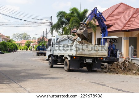 CHIANGMAI, SEPTEMBER 28: The worker controls the backhoe shovel to unload the soil on the truck on September 28, 2014 in Chiangmai, Thailand. - stock photo