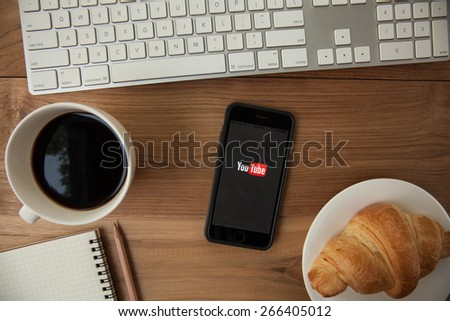 CHIANGMAI,THAILAND - APRIL 4, 2015: Brand new Apple iPhone 6 with YouTube app on the screen lying on desk with headphones. YouTube is the popular online video-sharing website, - stock photo