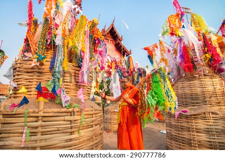 CHIANGMAI, THAILAND-APRIL 14 : Songkran Festival is celebrated in a traditional New Year's Day, A little monk comes to decorat tung in the temple Wat Phrasing. on April 14, 2010, Chiang Mai,Thailand. - stock photo