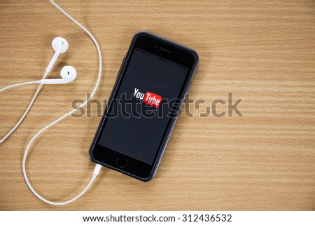 CHIANGMAI,THAILAND - AUGUST 31, 2015:Brand new Apple iPhone 5 with YouTube app on the screen lying on desk with headphones. YouTube is the popular online video-sharing website. - stock photo