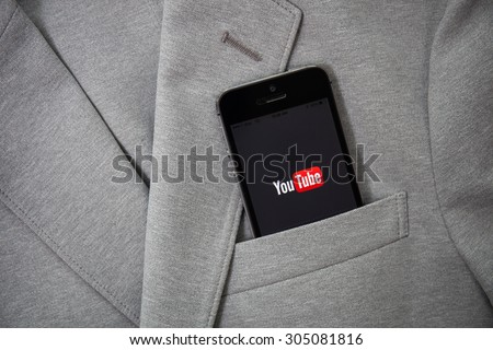 CHIANGMAI, THAILAND -AUGUST 11, 2015:Brand new Apple iPhone with YouTube app on the screen lying on desk with headphones. YouTube is the popular online video-sharing website, - stock photo