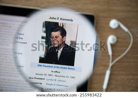 CHIANGMAI, THAILAND - February 26, 2015: Photo of Wikipedia article page about John F. Kennedy on a ipad monitor screen through a magnifying glass. - stock photo