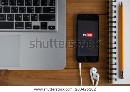 CHIANGMAI, THAILAND -JUNE 2, 2015:Brand new Apple iPhone with YouTube app on the screen lying on desk with headphones. YouTube is the popular online video-sharing website, - stock photo