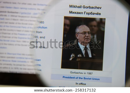 CHIANGMAI, THAILAND - March 5, 2015: Photo of Wikipedia article page of Mikhail Gorbachev on a ipad monitor screen through a magnifying glass. - stock photo