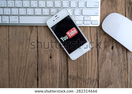 CHIANGMAI,THAILAND - MAY 28, 2015: Brand  Apple iPhone 4s with YouTube app on the screen lying on desk with headphones. YouTube is the popular online video-sharing website, - stock photo