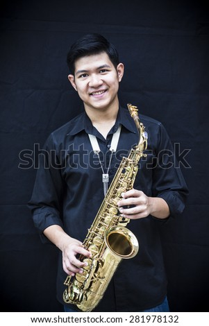 CHIANGMAI, THAILAND - MAY 28, 2015.  image of a handsome young man smiling while holding his  alto saxophone made  in France by selmer company at In  Grace Church Chiangmai, Thailand  - stock photo