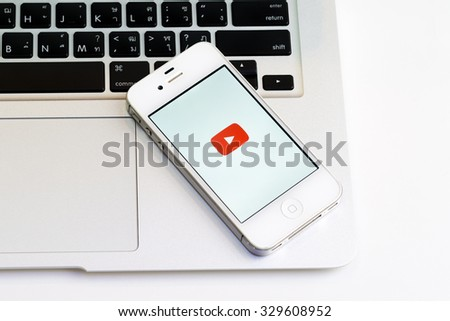 CHIANGMAI,THAILAND - October 20, 2015: Brand Apple iPhone 4s with YouTube app on the screen lying on desk with headphones. YouTube is the popular online video-sharing website, - stock photo