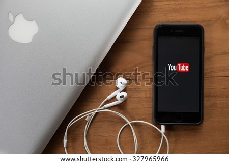 CHIANGMAI,THAILAND - OCTOBER 10, 2015:Brand new Apple iPhone 6 with YouTube app on the screen lying on desk with headphones. YouTube is the popular online video-sharing website, - stock photo
