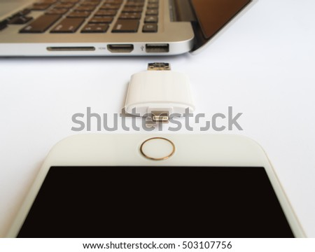 CHIANGRAI, THAILAND -SEPTEMBER 7, 2016: Close-up image of two way external flash storage between the Apple iPhone 6 and Apple Macbook Pro Retina on white background. Focus with USB connector.