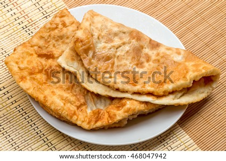 Chiburekki  is a deep-fried turnover with a filling of ground or minced meat and onions. It is made with a single round piece of dough folded over the filling in a half-moon shape.