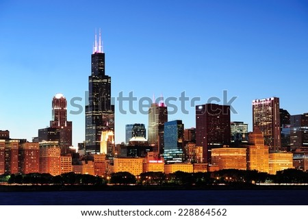 Chicago city downtown urban skyline at dusk with skyscrapers over Lake Michigan with clear blue sky. - stock photo