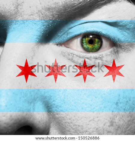 Chicago city flag painted on a man's face with a green eye to show Chicago support - stock photo