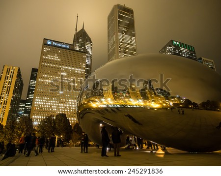 "Chicago, Illinois - Nov 27 :  Tourists visit The cloud gate or "" The bean"" landmark at night on November 27, 2014 at Millennium Park in Chicago, Illinois, USA. - stock photo"