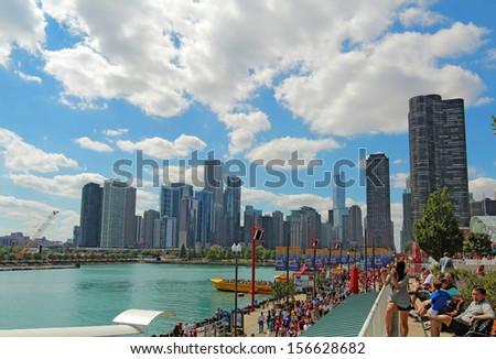 CHICAGO, ILLINOIS - SEPTEMBER 4: Tourists and a view of the cityscape at Navy Pier in Chicago, Illinois on September 4, 2011. The Pier is a popular destination with many attractions on Lake Michigan. - stock photo