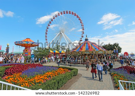 CHICAGO, ILLINOIS - SEPTEMBER 4: Tourists at the amusement park on Navy Pier in Chicago, Illinois on September 4, 2011. The Pier is a popular destination with many attractions on Lake Michigan. - stock photo