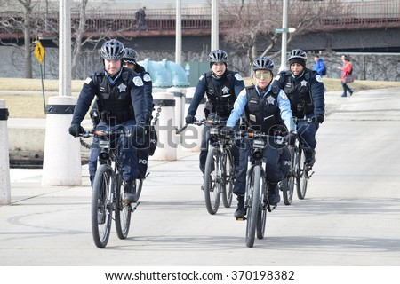 CHICAGO, ILLINOIS/USA â?? January 30, 2016: Chicago bicycle Police patrol lakefront trail by the Chicago Marine Safety Station by Dusable Harbor.  - stock photo