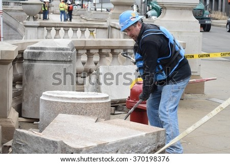 CHICAGO, ILLINOIS/USA â?? January 30, 2016: Stone mason uses pry bar to move rock slabs for third phase of Chicago riverwalk construction in Loop. - stock photo