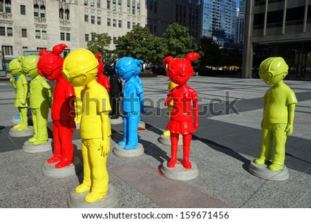 """CHICAGO, ILLINOIS/USA-OCTOBER 9:  On October 9, 2013, """"The Watch"""" a collection of 16 brightly-colored goggle-wearing child super hero figures went on display in Pioneer Court Plaza in Chicago. - stock photo"""