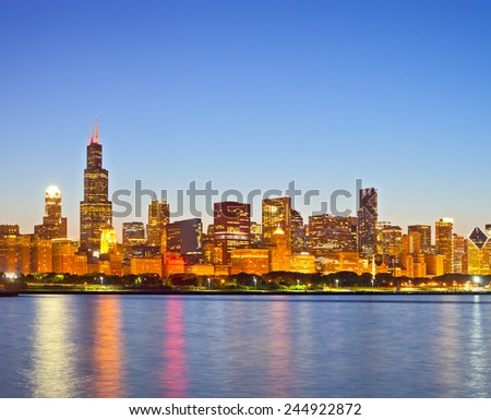Chicago Illinois USA, panorama of city downtown skyline at sunset with illuminated buildings, park and lake - stock photo