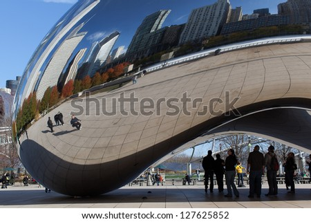 "CHICAGO - NOVEMBER 15: People admiring the Cloud Gate sculpture  in Millenium Park in Chicago on November 15, 2011. The sculpture is also known as ""The Bean"" because of its shape. - stock photo"