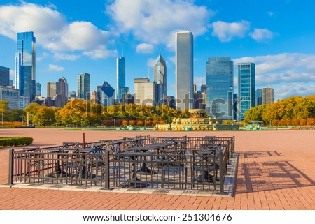 Chicago skyline after a clearing storm, Illinois. Tables and chairs sit in brick patio area of Grant Park, in the foreground. Buckingham fountain sits in the middle of the brick area. - stock photo