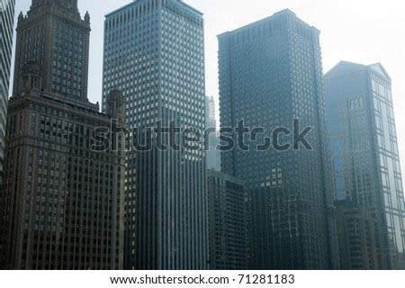 Chicago skyscrapers towering over the river in the morning mist - stock photo