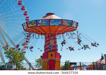 Chicago: wave swinger and Ferris Wheel at Navy Pier on September 22, 2014. Navy Pier was built in 1916, known as the famous landmark, is one of the most visited attraction in the entire Midwestern Usa - stock photo