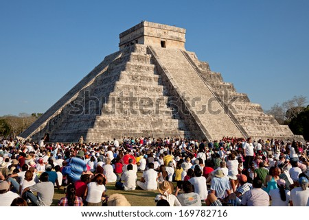 CHICHEN ITZA, MEXICO - MARCH 21: Group of tourists watching the feathered serpent crawling down the temple on Equinox March 21, 2011 in Chichen Itza, Mexico. This is one of the seven wonders of world. - stock photo