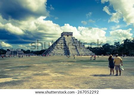 CHICHEN ITZA, MEXICO - NOVEMBER 29, 2012: anonymous tourists do sightseeing of Kukulkan pyramid in Chichen Itza, Mexico - stock photo