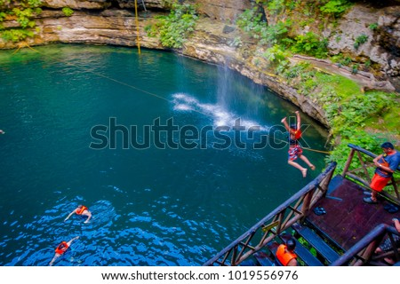 CHICHEN ITZA, MEXICO - NOVEMBER 12, 2017: Unidentified people swimming at Ik-Kil Cenote near Chichen Itza, Mexico. And enjoying the lovely cenote with transparent waters and hanging roots