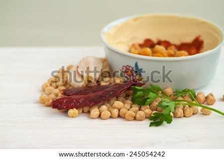 Chick peas and hummus dish on a vintage wooden background  - stock photo