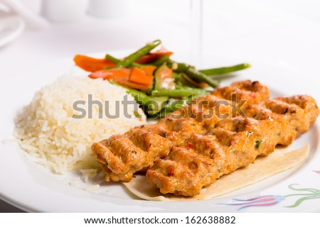 Chicken Adana kebap served with rice pilaf and green vegetables and some carrots - stock photo