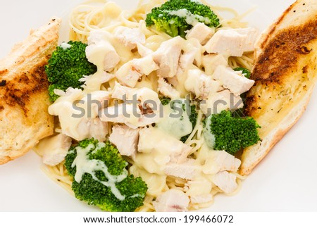 Chicken alfredo served with broccoli and garlic bread. - stock photo