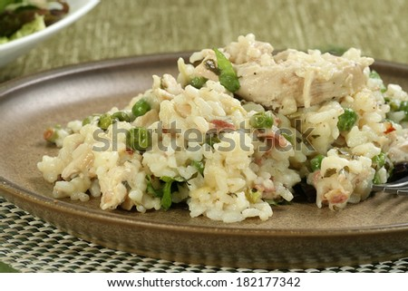 chicken and bacon risotto on a brown earthenware plate                                - stock photo