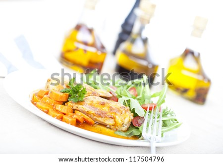Chicken and carrots on white plate - stock photo