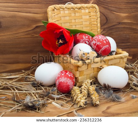 Chicken and Easter eggs in a basket with tulips on wooden background. - stock photo